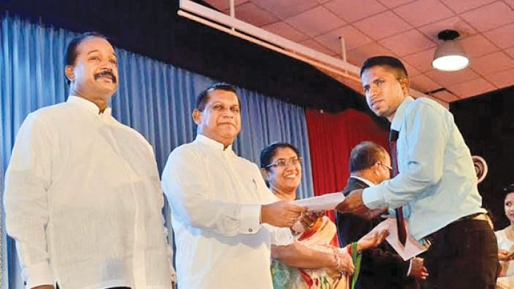 Public Administration and Management Minister Ranjith Madduma Bandara presenting an appointment letter to a graduate.
