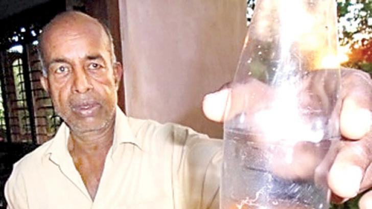 A resident of Galewela showing a bottle of contaminated water of a community water project.