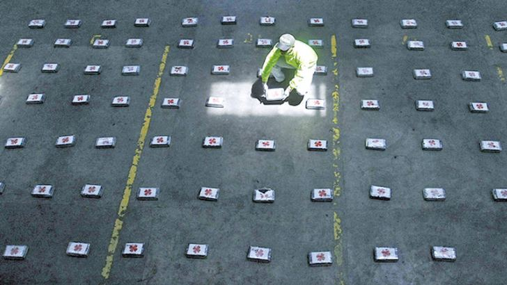 A Colombian official arranges bags of cocaine during a press conference in Medellin. - AFP