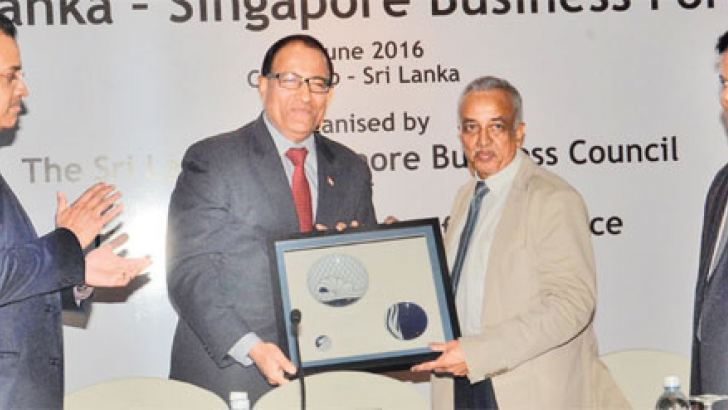 Development Strategies and International Trade Minister Malik Samarawickreme presenting a token of appreciation to Minister S Iswaran. BoI Chairman Upul Jayasuriya and Singapore Business Council Chairman Shamil Mendis look on. Picture by Wimal Karunathilake.