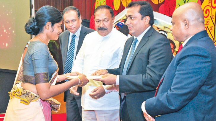 Education Minister Akila Viraj Kariyawasam handing over an appointment letter to a newly recruited officer to the SLEAS