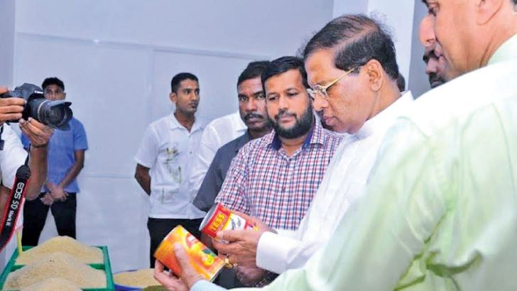 President Maithripala Sirisena, Minister Rishad Bathiudeen, former CWE Chairman Kiran Attapattu examining locally canned fish cans at a Sathosa outlet.