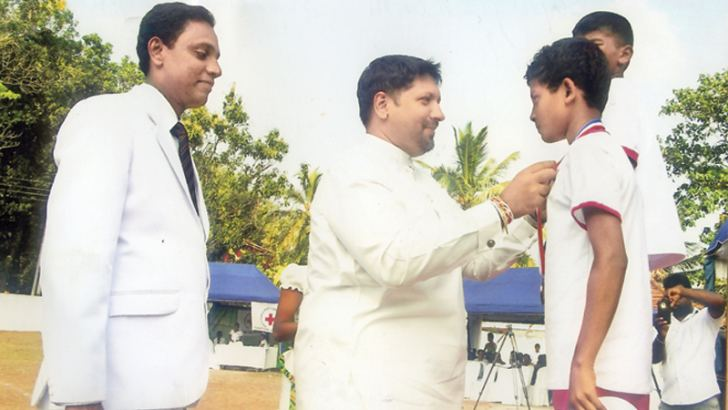 Here the Chief Guest Defence State Minister Ruwan Wijewardene pinning a medal on a student