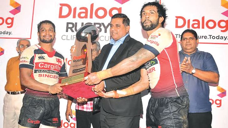 The victorious Kandy SC captain Rohan Weeraratne (left) along with his brother Gayan Weeraratne receive the Dialog Clifford Cup from Pradeep Keerthiratne, vice president, National Sales, Dialog Axiata PLC. Former Sri Lanka players Priyantha Ekananayake and Lasitha Gunaratne were also present.