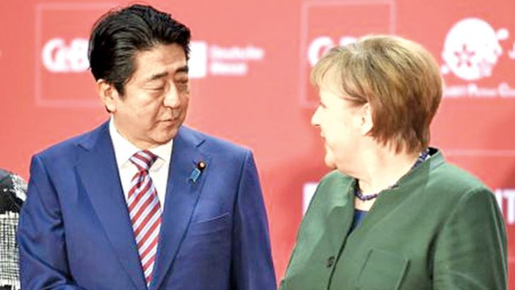 German Chancellor Angela Merkel and Japanese Prime Minister Shinzo Abe attend the opening ceremony of the CeBit computer fair.- AFP