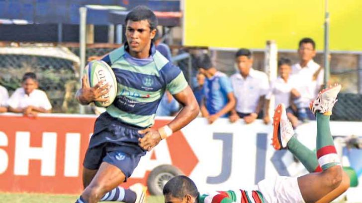 Wesley College winger Dineru Ranaweera (ball in hand) makes a daring run brushing aside a Zahira player who makes a valiant effort to stop him in their Singer 'A' division inter-schools league rugby match played at Longden Place yesterday. Pic by Hirantha Gunathilaka