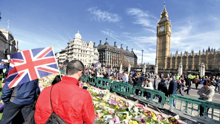 Floral tributes left in honour of the victims of the London terror attack on March 22, are pictured in Parliament Square in Westminster, London on Saturday during an anti-Brexit march.- AFP