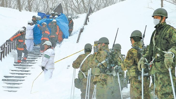 Firefighters carry a survivor they rescued from the site of an avalanche in Nasu town, Tochigi prefecture while Self Defense Force personnel look on. AFP