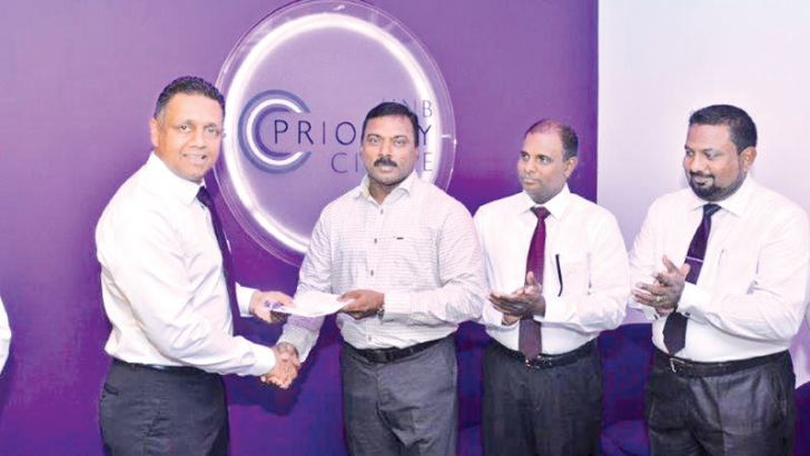 HNB  Retail and SME Banking Deputy General Manager Thimal Perera accepting the first deposit from Sivakumaran Nandakumaran. Head of Private Banking S Nandakumar and Jaffna Customer Centre Manager Vathulan Ganeshan look on.