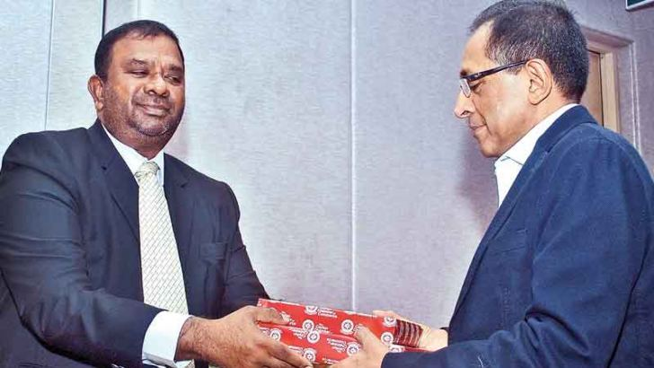 Ceylon Chamber of Commerce's Sri Lanka Malaysia Business Council President Asahiq Lafit handing over a token to Public Enterprise Development Minister Kabir Hashim. Picture by Siripala Halwala