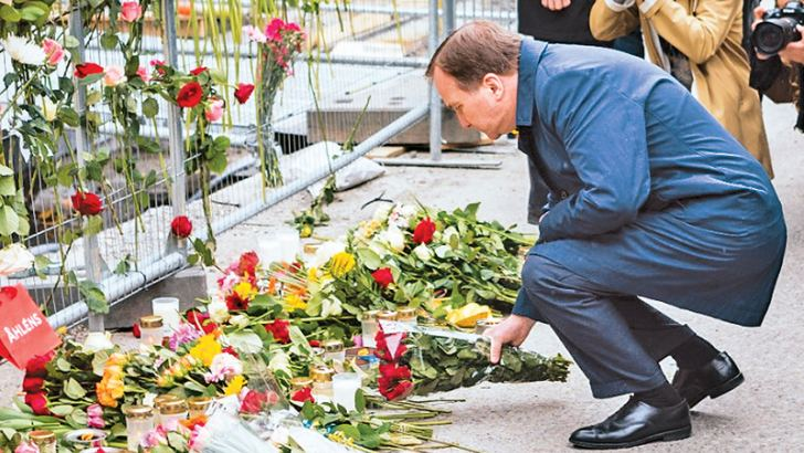 Swedish Prime Minister Stefan Lofven looks at flowers laid for the victims at the crime scene in central Stockholm.