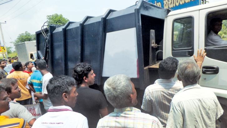 The decision to dump garbage in other locations in Colombo suburbs, following the calamity at Meethotamulla, drew public protests yesterday. Protesters blocked the Hanwella – Kirindiwela road preventing garbage trucks from reaching the waste management  unit at Maligawatta belonging to the Dompe Pradeshiya Sabha.  Picture by Somapala Theligama, Kirindiwela Corr.