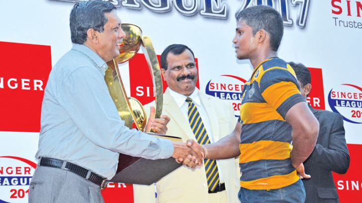 Royal skipper Ovin Askey is being congratulated by Marketing Director of Singer (Sri Lanka) Kumar Samarasinghe just before awarding the Singer League Champions trophy after Royal beat Trinity 22-17 in the first leg of the Bradby Shield watched by Royal principal B.A Abeyratne.
