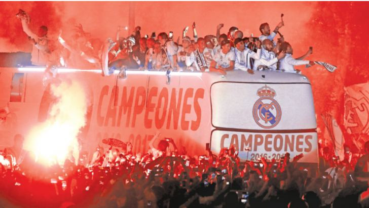 Real Madrid football team fans surround the bus as Real Madrid players celebrate the team's win on Plaza Cibeles in Madrid on May 22 after the Spanish league football match Malaga CF vs Real Madrid CF held at La Rosaleda stadium in Malaga on May 21. AFP