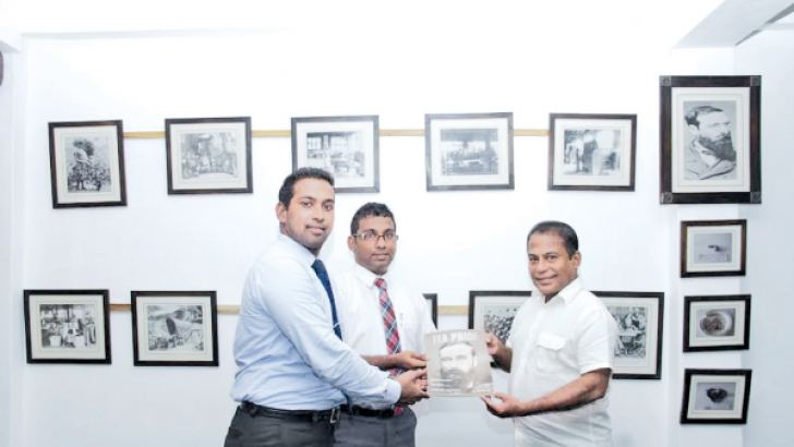 "Chairman Russel Perera presenting a copy of the ""Passion for Tea"" to Directors Jehan and Rashane Perera. Picture by Saliya Rupasinghe"