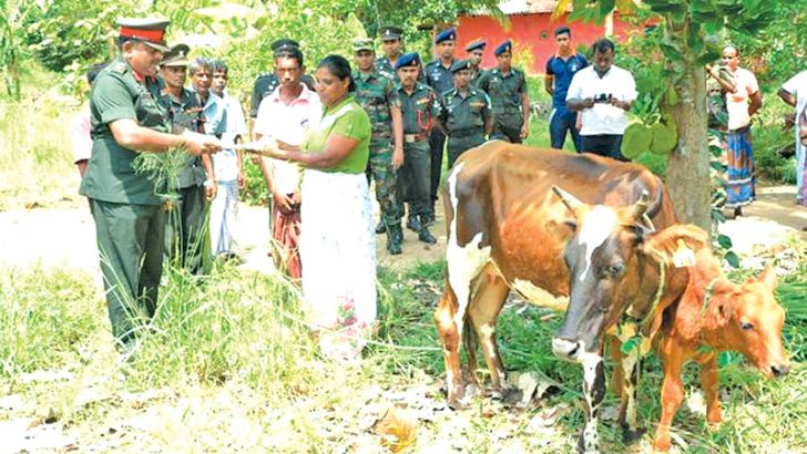 Director, Directorate of Agriculture and Livestock handing over ownership of the cow