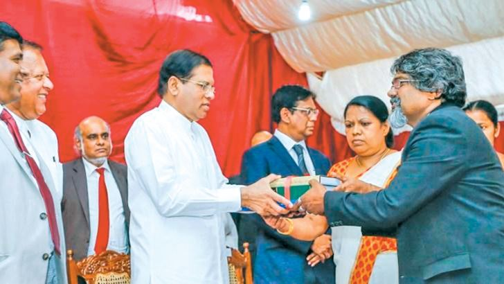 President Sirisena  presenting law books to members of the Lawyers' Bar Association.