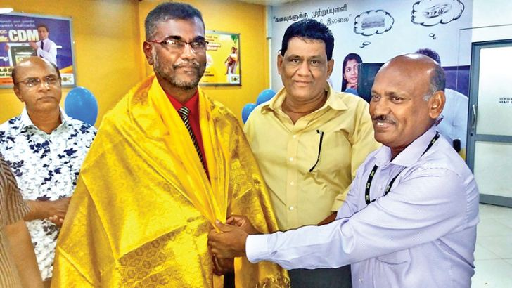 G. A. C. Rathnagee being honoured with a golden shawl by Kalmunai BoC Assistant Manager M. I. M. A. Nazeer.