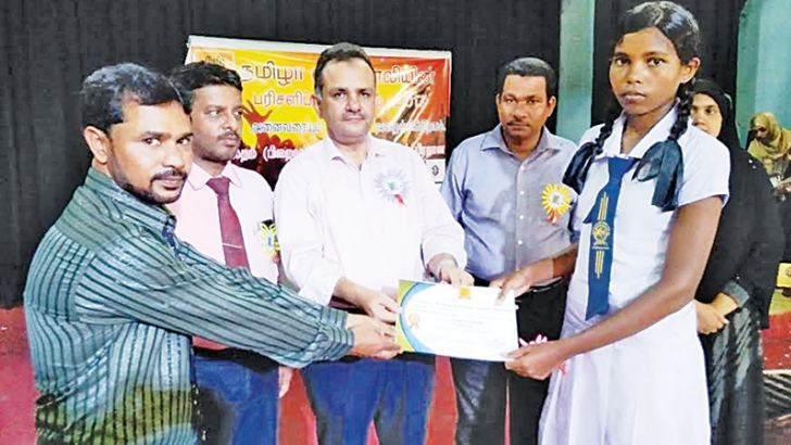 Chief guest Eastern Provincial Councilor I.L.M. Mahir awarding a prize to a winner