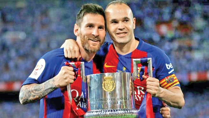 Barcelona's Lionel Messi and Andres  Iniesta celebrate with the trophy at the end  of the match