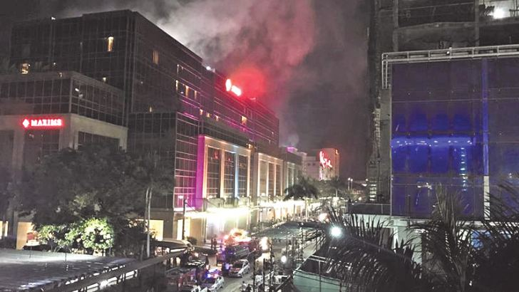 Smoke streamed from Resorts World Manila after a gunman apparently set fire to a gambling table. - AFP