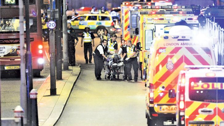 Police officers and members of the emergency services attend to a person injured in an apparent terror attack on London Bridge in central London on Saturday. - AFP