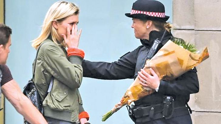 A Police woman with flowers comforts a woman on London Bridge.
