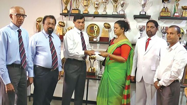 Old Antonian RAHL de Silva handing over the cheque to Thushara Roshini, mother of Santhush Ayeshmantha.