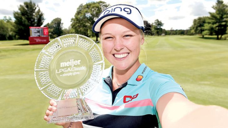 Brooke Henderson of Canada imitates a selfie as she poses with the championship trophy during the final round of the Meijer LPGA Classic at Blythefield Country Club on June 18 in Grand Rapids, Michigan. AFP