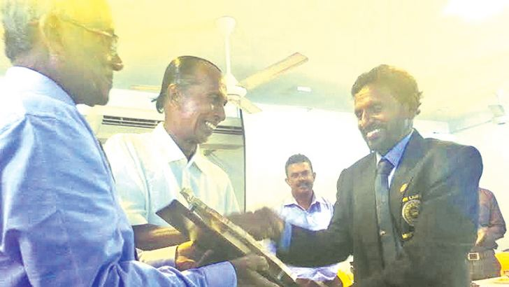 Y. K. Kularathne receiving a memento from K.K. Dharmadasa and Wimal Aluthpatabendi.