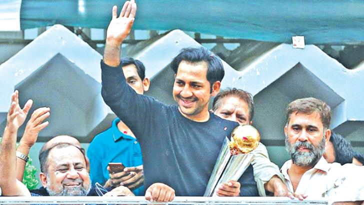 Sarfraz Ahmed gestures to cricket fans as he arrives at his home in Karachi with the ICC Champions Trophy. Pakistan beat India on Sunday to win the final.
