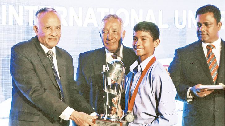 Amitha Dabare of CCC School of Cricket receives the award for the Player of the Tournament from the chief guest Anura Tennakoon. Nelson Mendis, the Director of Coaching of CCC School of Cricket looks on