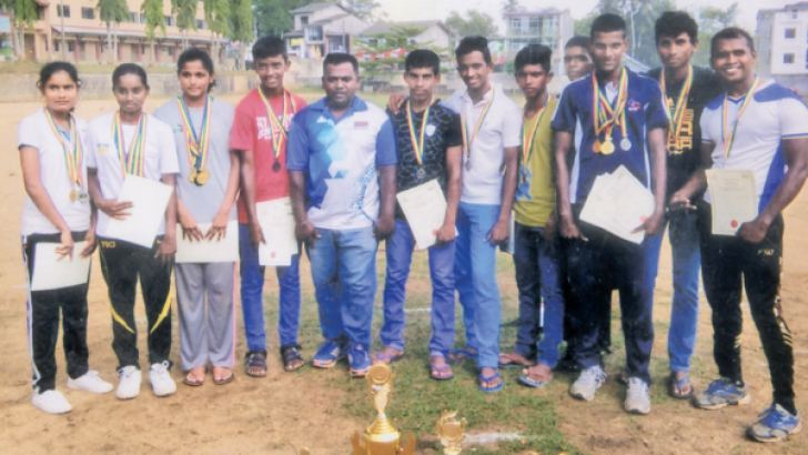 The member of Shiva Shakthi Sports Club, Poruwadanda, are seen hear with their certificates and cups, with their coach B Sudharshan (in the middle) who made a tremendous effort to win the Overall Sports Championship. (Pic Kalutara Central Special Correspondent H L Sunil Shantha.)