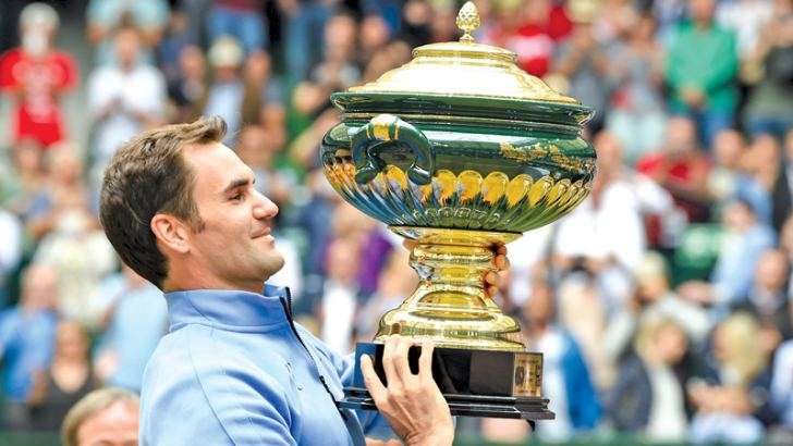 Roger Federer from Switzerland poses with his trophy after winning his final match against Alexander Zverev (not in picture) from Germany at the Gerry Weber Open tennis tournament in Halle, western Germany, on June 25. AFP