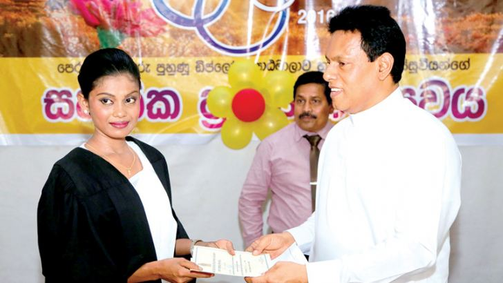 North Central Province Chief Minister Peshala Jayarathne Bandara handing over a diploma certificate to a pre-school teacher.