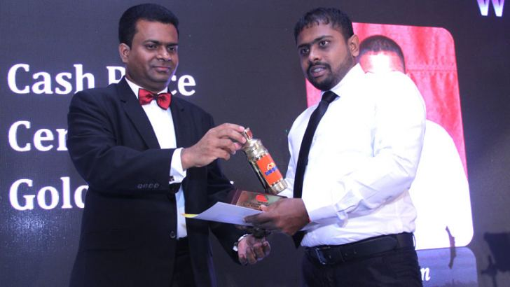 Executive Director of C. W. Mackie PLC - Mangala Perera handing over the Best Sales Representative Trophy to Sales Representative  Asen Thilakarathna.
