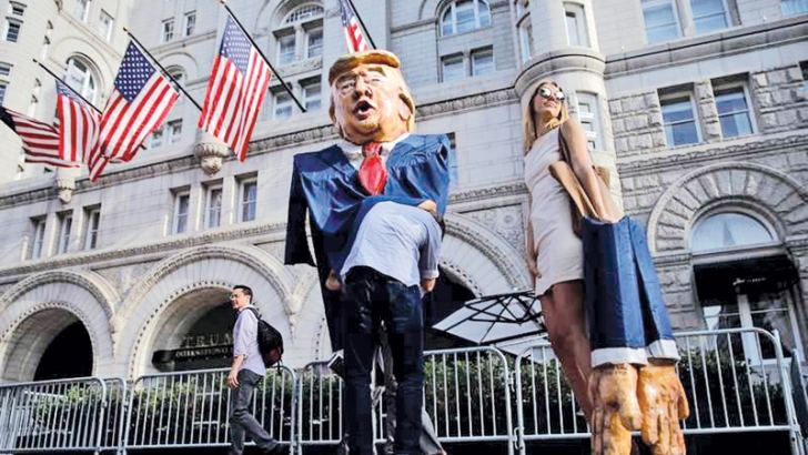 A woman impersonating Ivanka Trump stands next to a puppet of Donald Trump during a protest outside Trump International Hotel in downtown Washington on Wednesday.