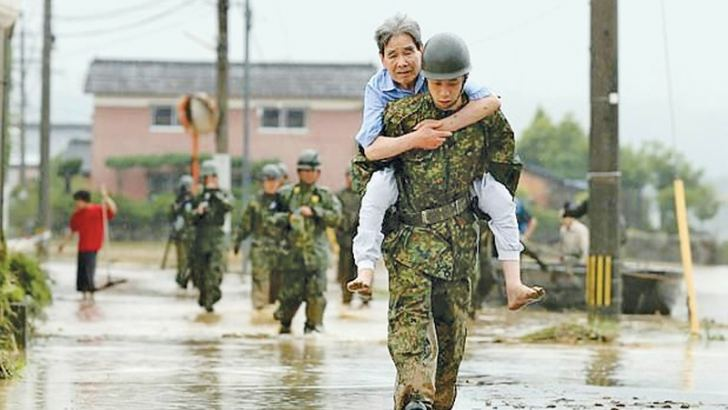 Japanese  soldiers help local  residents evacuate from flooded area in Asakura, Fukuoka  prefecture, yesterday.  -AFP
