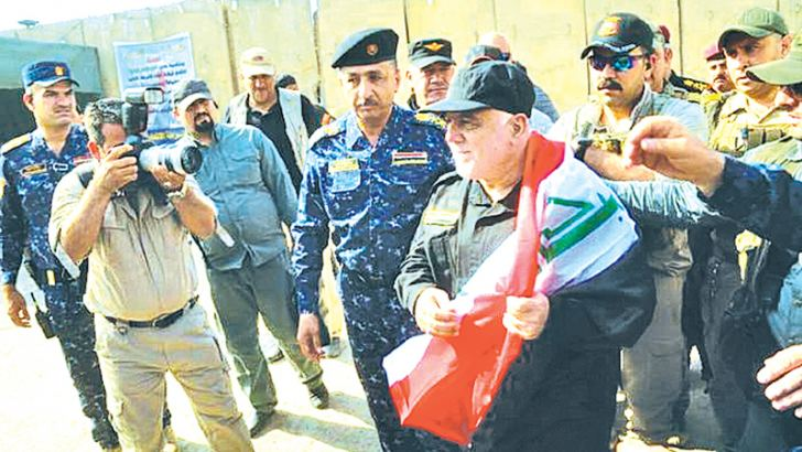 Iraqi Prime Minister Haider al-Abadi, (C), holds a national flag upon his arrival to Mosul, Iraq on Sunday, July 9, 2017. Backed by the U.S.-led coalition, Iraq.