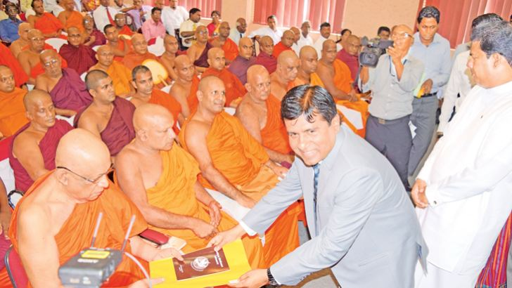 Appointment of Justice of Peace is bestowed upon a Buddhist monk by the Justice and Buddhasasana Minister Wijeyadasa Rajapakshe. Picture by Sudath Nishantha