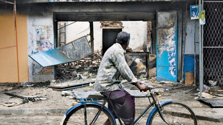 A man cycles past Tamil-owned stores that were set ablaze by a mob in Trincomalee on May 7, 2006. -The New York Times