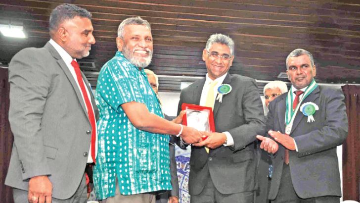 Minister Faiszer Musthapha handing over an award to Elections Commissioner Mahinda Deshapriya appreciating his service