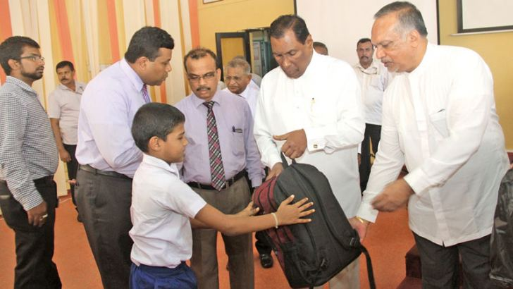 Labour and Trade Union Relations Minister W.D.J.Seneviratne and State Minister Ravindra Samaraweera hand over scholarship and the school equipment to a child.