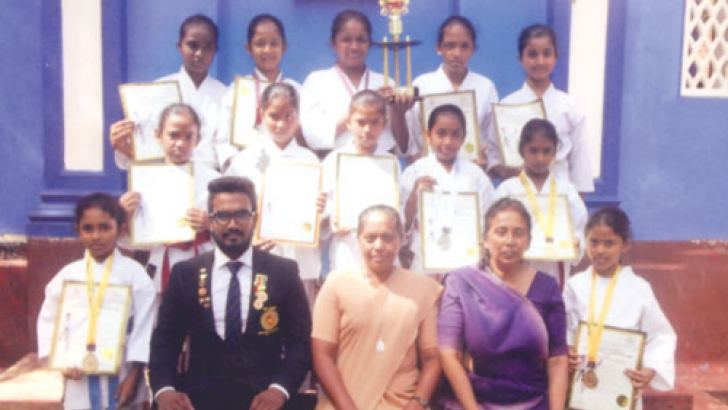 The HFC Kirimetiyagara karatekas Rithmi Amidon, Ushadi Hansika, Venuri Supunya, Gagani Sandamini, Kawmini Nirasha, Kalashi Tharanga, Sathsarani Wijewardhana, Imesha Lakshani, Rashini Sanjana, Amasha Shenali, Sugandhi Yosodara and Hasini Dinu with the principal, Sister, Sheelani Pau, Sports Instructor (Mrs) Priyadharshani Meewaddana and coach, Shehan de Silva. Picture by Mahanama Vithanage, Malwana Group Correspondent