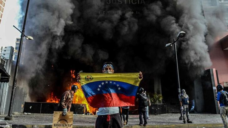 Anti-government demonstrators attack the administration headquarters of the Venezuelan Supreme Court of Justice as part of protests against President Nicolas Maduro in Caracas.