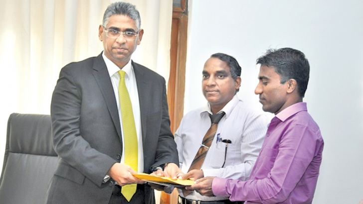 Minister Faiszer Musthapha receiving the document.