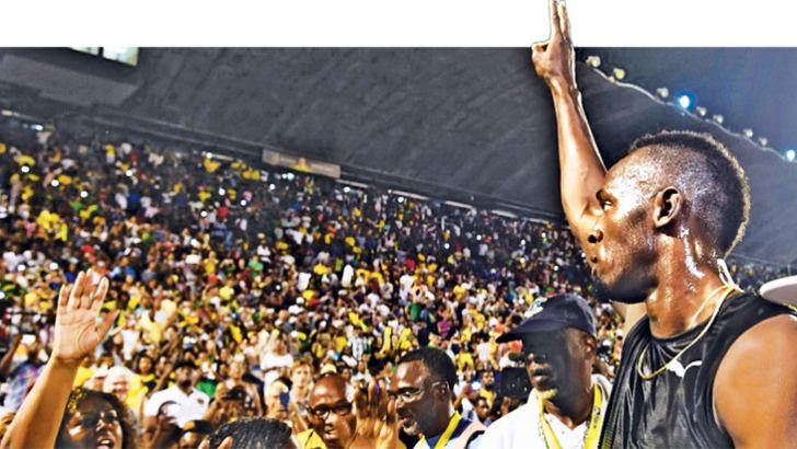 """Usain Bolt of Jamaica salutes the crowd after winning 100m """"Salute to a Legend"""" race during the Racers Grand Prix at the national stadium in Kingston"""