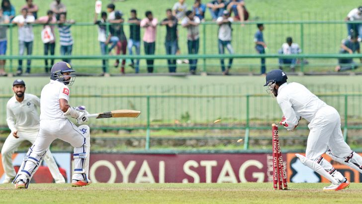 Niroshan Dickwella is stumped by Wriddhiman Saha off Kuldeep Yadav for 29 on the second day of the third and final Test at the Pallekele International Stadium yesterday. Pictures by Rukmal Gamage