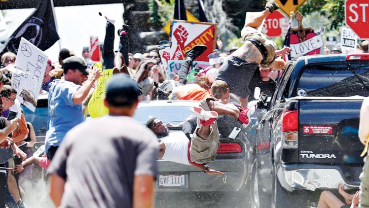 People fly into the air as a vehicle drives into a group of protesters demonstrating against a white nationalist rally in Charlottesville, Virginia, Saturday. -AFP