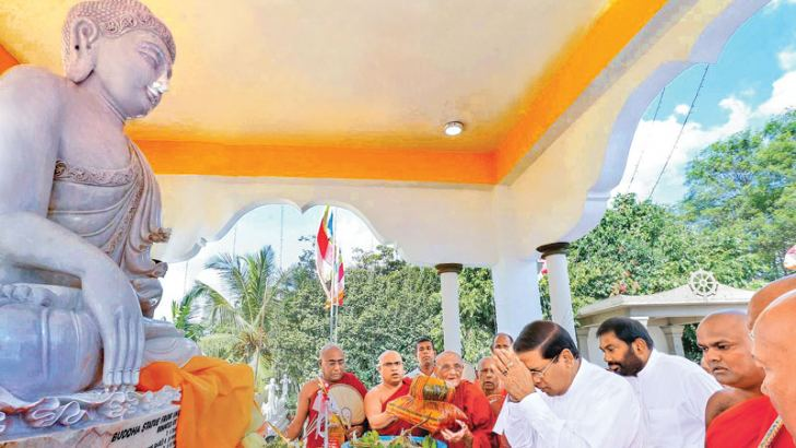President Sirisena laying floral tributes at the newly built Buddha statue